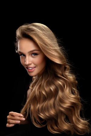 Krullend blond haar. Beauty Model meisje met een perfecte make-up, Gorgeous Volume en haarkleur permanent op zwarte achtergrond. Mooie Glimlachende Vrouw Met Gezond Lang glanzend golvende haar portret. Hoge kwaliteit