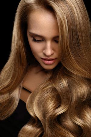Volume cheveux. Belle femme avec beauté visage, maquillage parfait, cheveux longs ondulés brillants en bonne santé sur fond noir. Modèle sexy fille avec la mode coiffure et magnifique couleur de cheveux blonds. Haute résolution