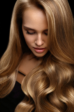 Volume cheveux. Belle femme avec beauté visage, maquillage parfait, cheveux longs ondulés brillants en bonne santé sur fond noir. Modèle sexy fille avec la mode coiffure et magnifique couleur de cheveux blonds. Haute résolution Banque d'images - 70474556