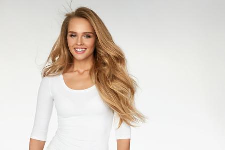Schönheit. Schöne Frau mit perfekten langen blonden Wellig, lockiges Haar, das auf weißem Hintergrund. Portrait des glücklichen Mädchens mit Fit Sexy Body und natürliche Gesicht Make-up. Health-Konzept. Hohe Auflösung