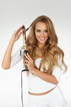 巻き毛。カーリング アイロンを使用して、それをアイロン ブロンドの長いウェーブのかかった髪と美しい笑顔の女性。完璧なカーラーを使用して豪