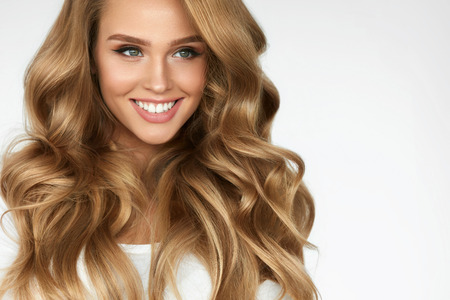 Beautiful Curly Hair. Smiling Girl With Healthy Wavy Long Blonde Hair. Portrait Happy Woman With Beauty Face, Sexy Makeup And Perfect Hair Curls. Volume, Hairstyle, Hairdressing Concept. High Quality 免版税图像