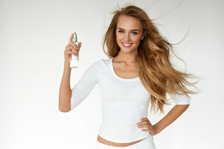Hair Cosmetics. Smiling Woman With Healthy Beautiful Long Wavy Hair Applying Thermal Protect Hair Spray. Happy Girl With Blonde Smooth Hair Using Heat Protect Spray. Haircare Cosmetic. High Resolution