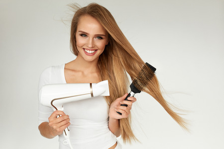 Hair Care. Woman Drying Beautiful Long Straight Hair Using Dryer. Portrait Of Attractive Girl Model With Blonde Hair Using Hairdryer,  Round Brush For Hairdressing. Hairstyle Concept. High Resolution