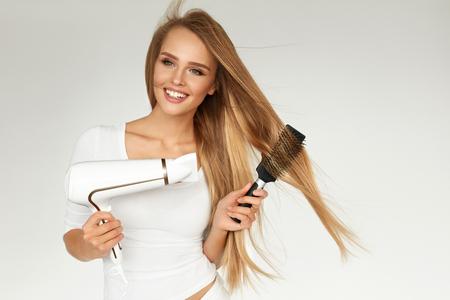 髪のケア。乾燥乾燥機を使用して美しいストレートのロングヘアの女性。丸い理髪用ブラシ、ドライヤーを使用してブロンドの髪を持つ魅力的な女