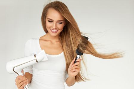 헤어 케어. 건조기를 사용 하여 건조 아름다운 긴 스트레이트 헤어. 금발 헤어 미용 헤어 드라이어, 둥근 브러시를 사용 하여 매력적인 여자 모델의 초