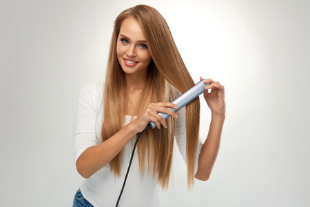 ストレートの髪。美しい笑顔の女性平らな鉄、健康的なブロンドの長い髪を矯正ストレートヘア アイロン。肖像画の豪華な女の子モデル アイロン髪 写真素材