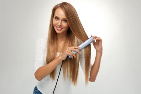Stijl haar. Mooie Glimlachende Vrouw Straightening Gezond Lang Blond Haar met Flat Iron, Hair Straightener. Portret Schitterend Meisje Model Strijkservice Hair. Schoonheid, kapsel concept. Hoge resolutie Stockfoto