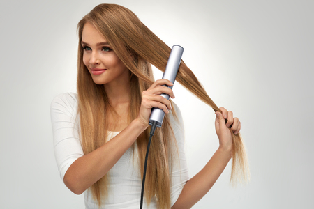 Straight Hair. Beautiful Smiling Woman Straightening Healthy Long Blonde Hair With Flat Iron, Hair Straightener. Portrait Gorgeous Girl Model Ironing Hair. Beauty, Hairstyle Concept. High Resolution Stock Photo