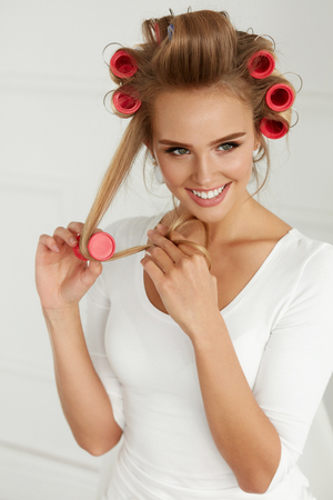 Hairdressing. Happy Woman Applying Hair Rollers On Beautiful Healthy Blonde Hair. Attractive Smiling Girl With Hair Curlers On Head Curling Hair For Perfect Curls. Hairstyle. Beauty. High Resolution Imagens