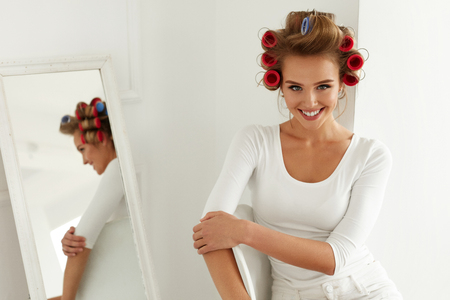 getting ready: Woman Getting Ready. Beautiful Happy Female Model With Hair Rollers On Healthy Blonde Hair Indoors. Attractive Smiling Girl With Hair Curlers On Head Curling Hair. Hairstyle, Haircare. High Resolution