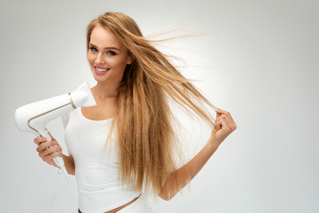 Woman Drying Hair Using Hair Dryer. Beautiful Smiling Girl With Blonde Long Straight Hair Using Hairdryer. Portrait Of Happy Female Using Blow Hair Dryer. Hairstyle, Hair Care Concept. High Resolution