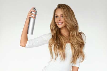 Hairstyle. Woman Spraying Hairspray On Beautiful Long Curly Hair On White Background. Attractive Smiling Girl With Blonde Shiny Wavy Hair Using Spray For Styling, Hairdressing. Beauty. High Resolution