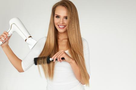 secador de pelo: Peluquería. Hermosa mujer que seca el pelo recto largo sano Uso de secador de soplado. Atractivo de la muchacha sonriente con el pelo rubio Uso de secador de pelo y cepillo redondo seco. Concepto de cuidado del cabello. Alta resolución Foto de archivo
