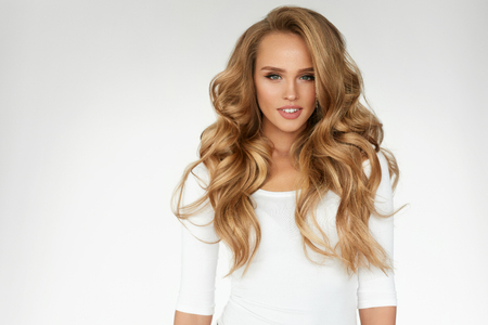 Beautiful Curly Hair. Smiling Girl With Healthy Wavy Long Blonde Hair. Portrait Happy Woman With Beauty Face, Sexy Makeup And Perfect Hair Curls. Volume, Hairstyle, Hairdressing Concept. High Quality Stockfoto