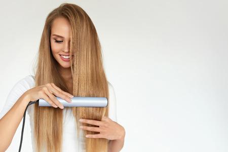 이발. 머리 직선기를 사용 하여 아름 다운 긴 직선 머리를 가진 여자. 화려한 웃는 소녀 직선와 함께 건강 한 금발의 머리카락을 교정기. 헤어 다림 질,