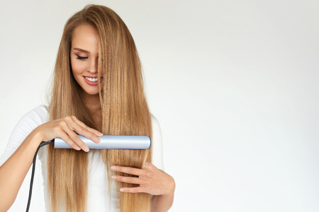 Hairdressing. Woman With Beautiful Long Straight Hair Using Hair Straightener. Gorgeous Smiling Girl Straightening Healthy Blonde Hair With Flat Iron. Hair Ironing, Hairstyle Concept. High Resolution Archivio Fotografico