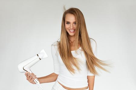 Haardroger. Mooie Glimlachende Vrouw Drogen Gezond Lang Recht Haar behulp Föhn. Portret Aantrekkelijk Gelukkig meisje met blond haar doet haarstijl. Kappers, Hair Care Concept. Hoge resolutie Stockfoto