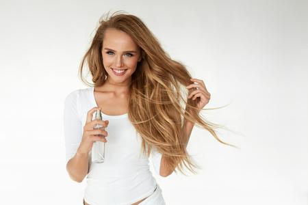 Haarkosmetik. Lächelnde Frau mit gesunden Schöne gewellte lange Haare Anwendung Thermal Protect Haarspray. Glückliches Mädchen mit dem blonden glattes Haar unter Verwendung von Wärme Spray schützen. Haircare Kosmetik. Hohe Auflösung Standard-Bild - 70476507