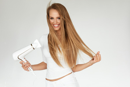 Hair Dryer. Beautiful Smiling Woman Drying Healthy Long Straight Hair Using Hairdryer. Portrait Attractive Happy Girl With Blonde Hair Doing Hairstyle. Hairdressing, Hair Care Concept. High Resolution