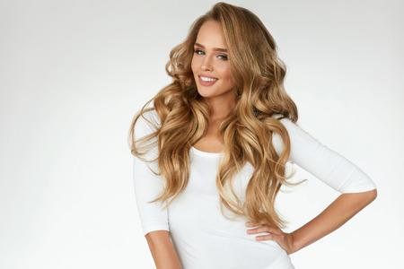 Lindo cabelo encaracolado. Menina de sorriso com cabelo louro longo ondulado saudável. Retrato mulher feliz com rosto de beleza, maquiagem sexy e cachos de cabelo perfeito. Volume, penteado, conceito de cabeleireiro. Alta qualidade