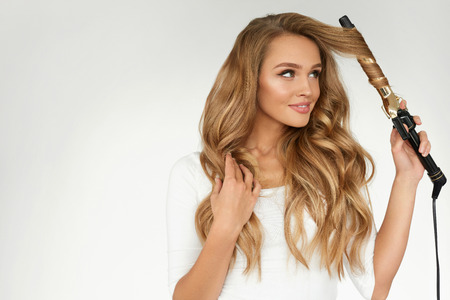 Curly Hair. Beautiful Smiling Woman With Long Blonde Wavy Hair Ironing It, Using Curling Iron. Happy Girl With Gorgeous Healthy Smooth Hair Using Curler For Perfect Curls. Hairstyle And Hairdressing