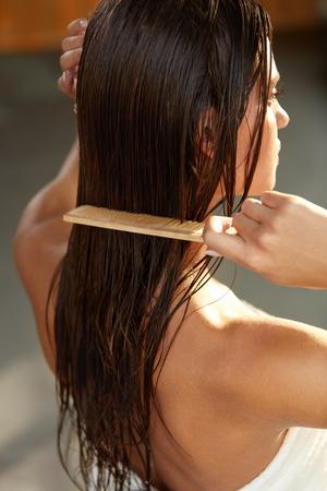 모발 관리. 목욕 머리 썹 건강한 스트레이트 갈색 머리 후 아름 다운 여자의 근접 촬영. 나무 빗 가진 그녀의 오래 젖은 머리를 솔 질하는 젊은 여자. 건