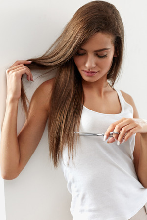 Split End Problems. Closeup Of Beautiful Sexy Young Woman With Long Natural Straight Hair With Scissors In Hand. Female Model Cuts Split-Ended Hair. High Resolution Image
