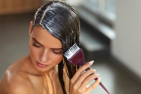 髪のマスキング。長い健康的な髪に自然なマスクを適用することの手でブラシを持つ若い女性。美しい少女の濡れた髪にコンディショナーを広がっ