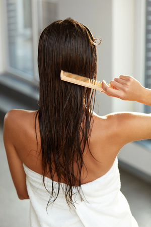Haircare. Closeup Of Female Model Brushing Beautiful Long Healthy Hair With Brush. Brunette Young Woman Brushes Wet Hair With Wooden Comb. Hair Health And Beauty Concept. High Resolution Image