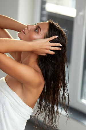 Hair Beauty. Closeup Of Young Female Model In Towel After Bath. Beautiful Sexy Woman With Long Wet Healthy Hair Holding It In Hands In Bathroom. Body Care, Hair Care Concept. High Resolution Image