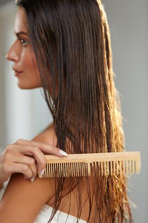 cabello: Cuidado del cabello. Detalle de la hermosa muchacha después del baño recta Hairbrushing saludable Cabello castaño. Joven cepillarse el pelo largo húmedo con el peine de madera. Concepto de salud y belleza. Imagen de alta resolución Foto de archivo