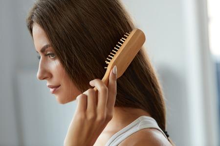Haarpflege. Closeup der schönen Frau Hairbrushing Hair mit Pinsel. Portrait Of Sexy Weibliche Frau Bürsten Lange Gerade Gesundes Haar Mit Haarbürste. Gesundheit und Schönheit Konzept. Hochauflösendes Bild