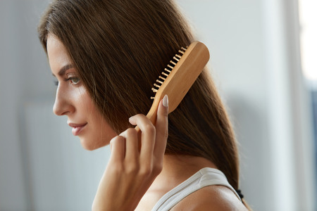 Haarverzorging. Close-up van mooie vrouw haar met borstel borstel. Portret van Sexy Vrouwelijke Vrouw die Lang Recht Gezond Haar met Haarborstel borstelen. Gezondheid en schoonheid Concept. Hoge resolutie afbeelding