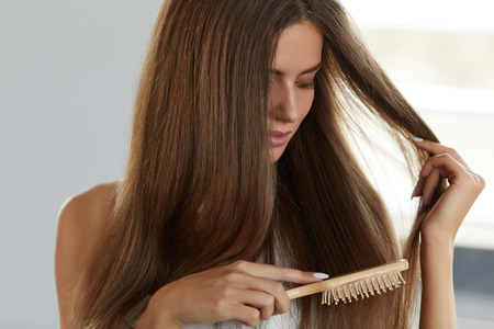 Hair Care. Closeup Of Beautiful Woman Hairbrushing. Portrait Of Sexy Female Model Brushing Shiny Long Straight Healthy Hair With Hairbrush. Health And Beauty Concept. High Resolution Image Stock Photo