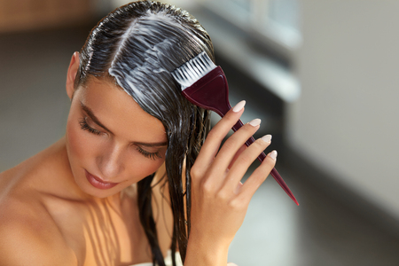 Hair Masking. Young Woman With Brush In Hand Applying Natural Mask On Long Healthy Hair. Beautiful Girl Spreading Conditioner Along Wet Hair. Health And Beauty. High Resolution Image Stock Photo