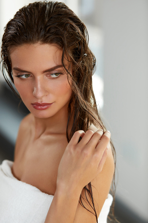 Hair And Body Care. Portrait Of Beautiful Young Female Model After Bath. Closeup Of Sexy Woman In Towel With Wet Long Hair And Hand Near Face. Health And Beauty Concept. High Resolution Image Stock Photo