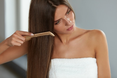 Brushing Hair. Portrait Of Sexy Young Woman Brushing Straight Natural Hair With Comb. Closeup Of Girl Combing Beautiful Long Healthy Hair With Hairbrush. Hair Care And Beauty Concept. High Resolution