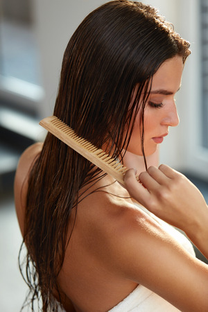 Hair Care. Closeup Of Beautiful Girl After Bath Hairbrushing Healthy Straight Brown Hair. Young Woman Brushing Her Long Wet Hair With Wooden Comb. Health And Beauty Concept. High Resolution Image