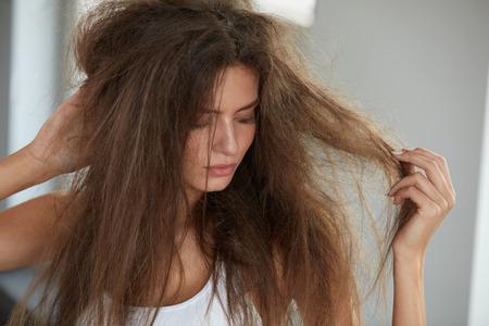 Zniszczone włosy. Piękne Sad młoda kobieta z długimi potargane włosy. Zbliżenie portret kobiet modelu gospodarstwa Messy unbrushed suche włosy w ręce. Uszkodzenia włosów, zdrowie i uroda Concept. Wysoka rozdzielczość