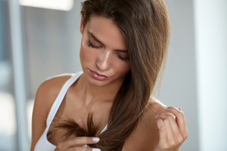 Health And Beauty. Portrait Of Beautiful Sad Young Woman With Long Hair In Hand. Closeup Of Unhappy Female Model Looking At Split Ended Hair. Hair Care Concept. High Resolution Image Stock Photo