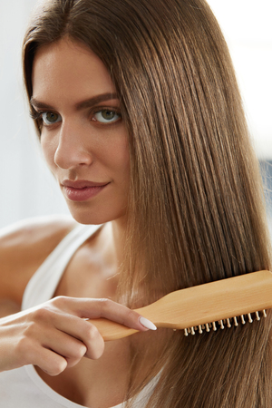 feminine beauty: Hair Care. Closeup Of Beautiful Woman Hairbrushing. Portrait Of Sexy Female Model Brushing Shiny Long Straight Healthy Hair With Hairbrush. Health And Beauty Concept. High Resolution Image Stock Photo