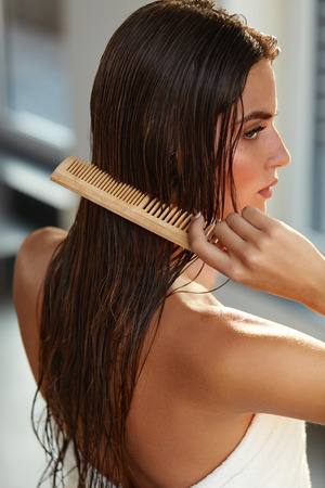 Hair Care. Closeup Of Beautiful Girl After Bath Hairbrushing Healthy Straight Brown Hair. Young Woman Brushing Her Long Wet Hair With Wooden Comb. Health And Beauty Concept. High Resolution Image Imagens - 70675761