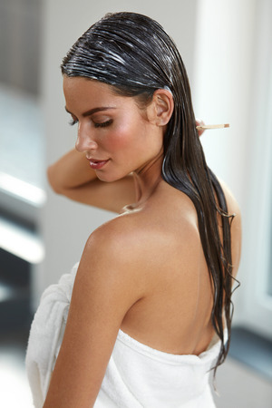 hair conditioner: Hair Beauty. Closeup Of Beautiful Woman Hairbrushing With Comb And Using Conditioner. Young Female Model Putting Refreshing Mask On Long Wet Hair With Wooden Comb. Health Care. High Resolution