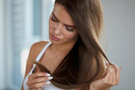 건강과 아름다움. 손에 긴 머리를 가진 아름 다운 슬픈 젊은 여자의 초상화. 분할 된 끝 머리를 찾고 불행한 여성 모델의 근접 촬영. 헤어 케어 개념입