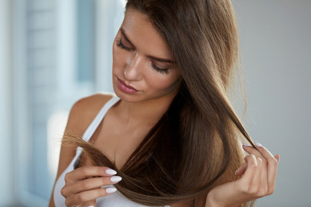 Health And Beauty. Portrait Of Beautiful Sad Young Woman With Long Hair In Hand. Closeup Of Unhappy Female Model Looking At Split Ended Hair. Hair Care Concept. High Resolution Image Archivio Fotografico