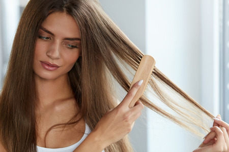 Woman Health And Beauty. Portrait Of Beautiful Sexy Young Female Model With Hairbrush In Hand. Closeup Of Girl Brushing Shiny Long Hair Using Wooden Brush, Getting Rid Of Tangles. High Resolution