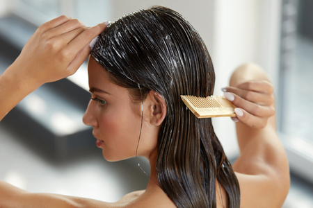 Hair Beauty. Closeup Of Beautiful Woman Hairbrushing With Comb And Using Conditioner. Young Female Model Putting Refreshing Mask On Long Wet Hair With Wooden Comb. Health Care. High Resolution