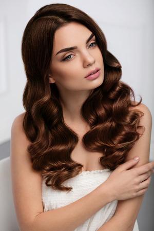 곱슬 머리 스타일. 긴 빛나는 물결 모양의 헤어 스타일 아름 다운 갈색 머리 여자 모델입니다. 천연 화장과 화려한 여자, 아름다움 얼굴, 건강한 소프트