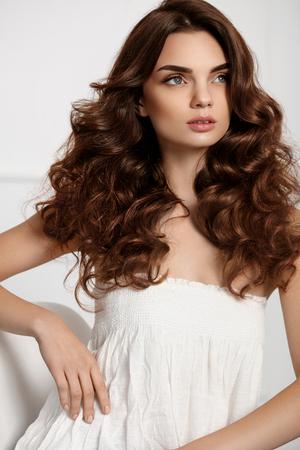髪のスタイル。健康の長い波状毛と豪華な顔メイク美人。ファッション髪型、茶色の髪の色と完璧なカールとブルネットの少女モデルの肖像画。美 写真素材